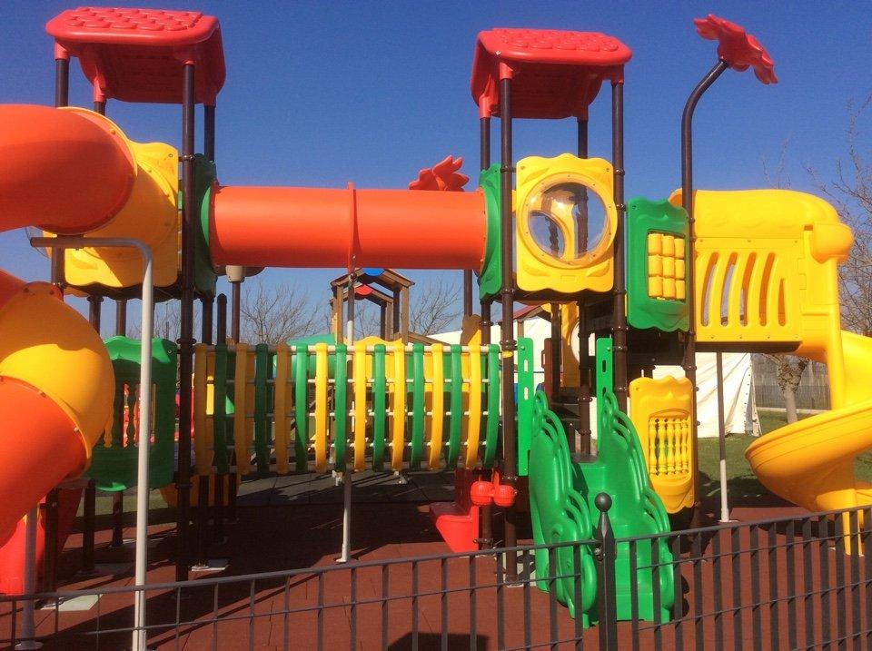 un'area giochi per bambini dotata di scivoli, gonfiabili e attrazioni varie, nel parco esterno