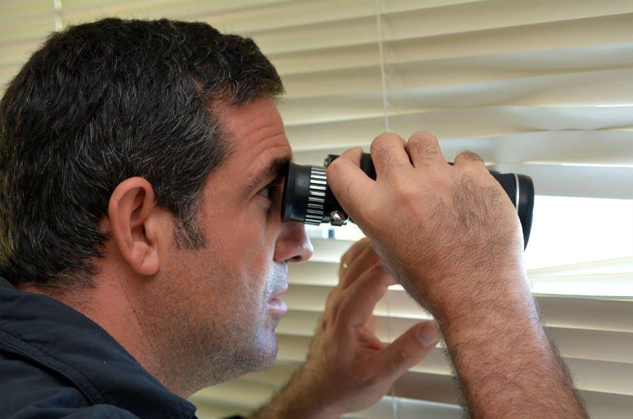 Uomo che spia da una finestra con un binocolo