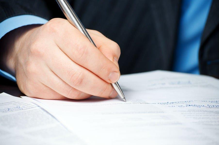 Mano di un uomo mentre firma un documento