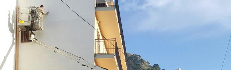 Operaio carteggia una parete esterna su una piattaforma elevatrice
