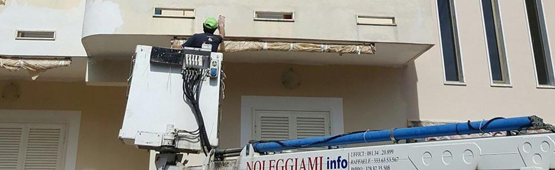 Operaio carteggia una parete esterna sulla piattaforma elevatrice