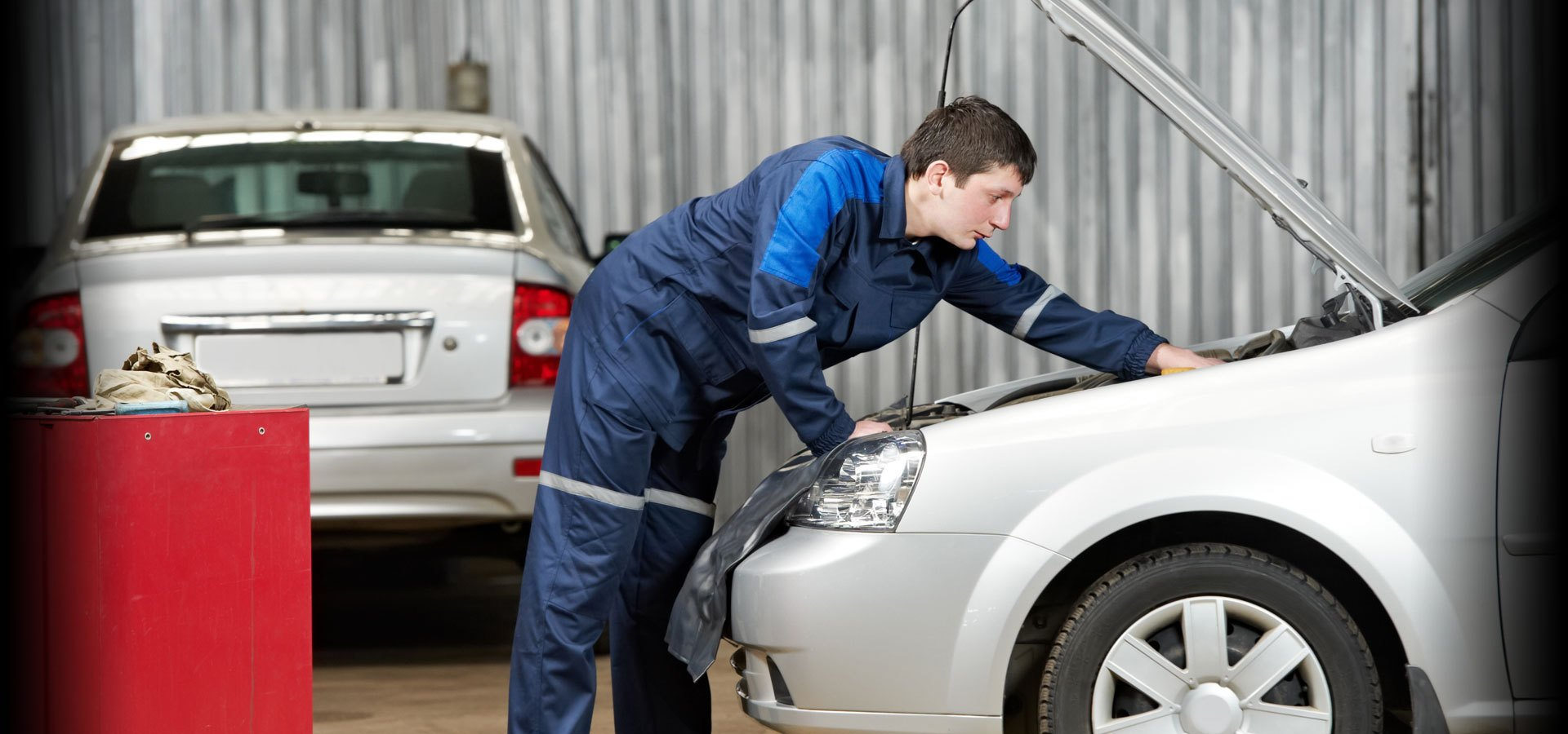 Mechanic in blue overalls working on a car