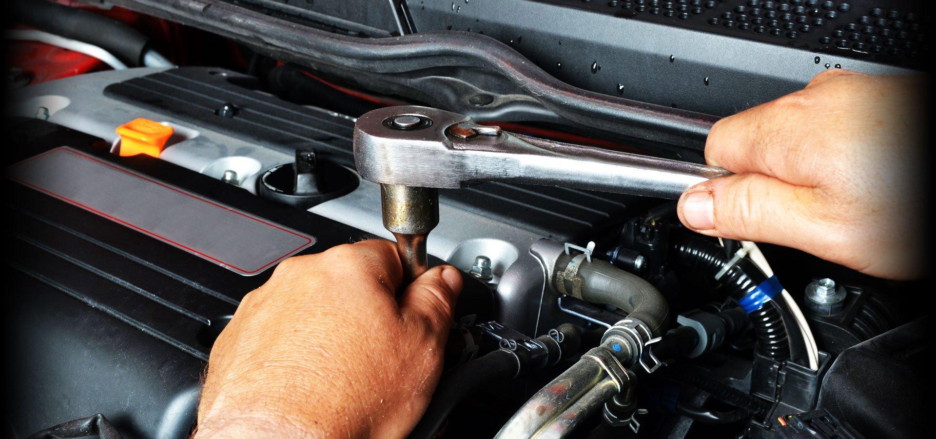 Hands of a mechanic repairing an engine