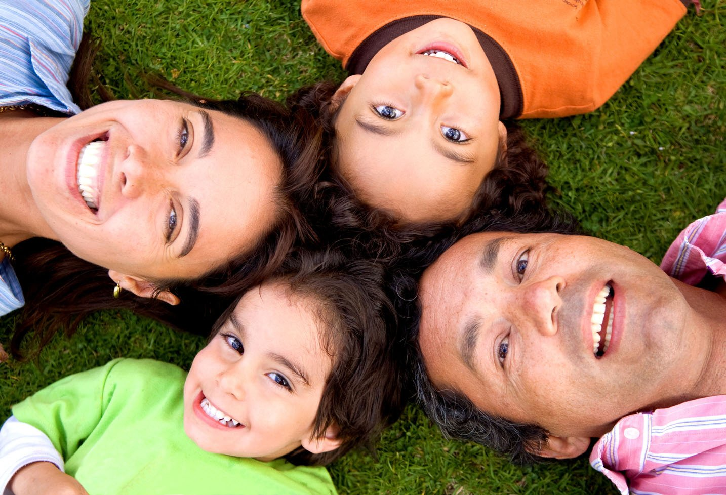 A literal family circle - parents and two children lying on grass in a circle