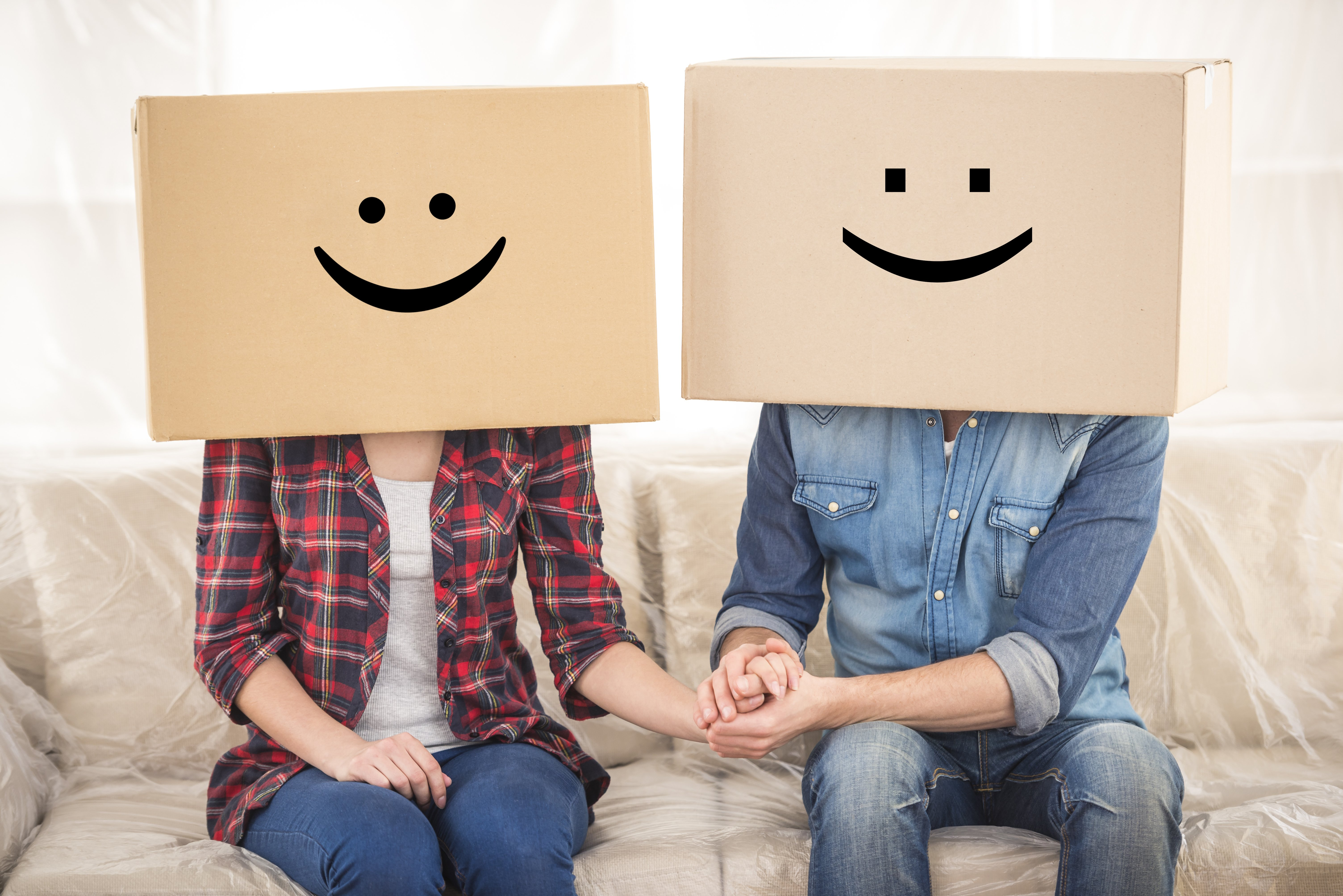 A couple holding hands on a cream sofa, wearing boxes with smiley faces over their heads