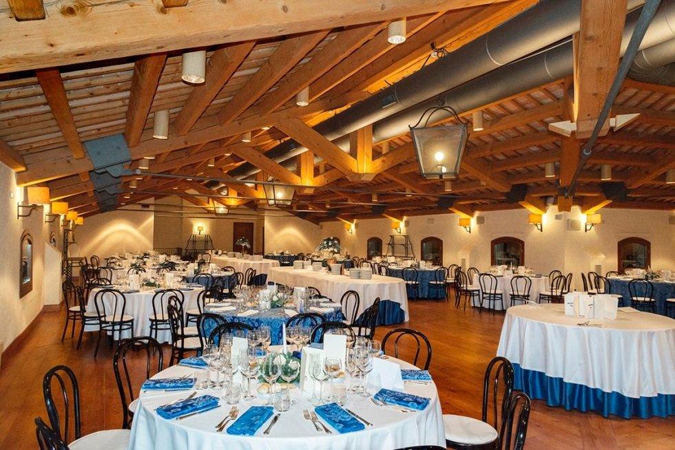 vista interna di un ristorante con soffitto in legno e tavoli apparecchiati  per festa -veduta laterale