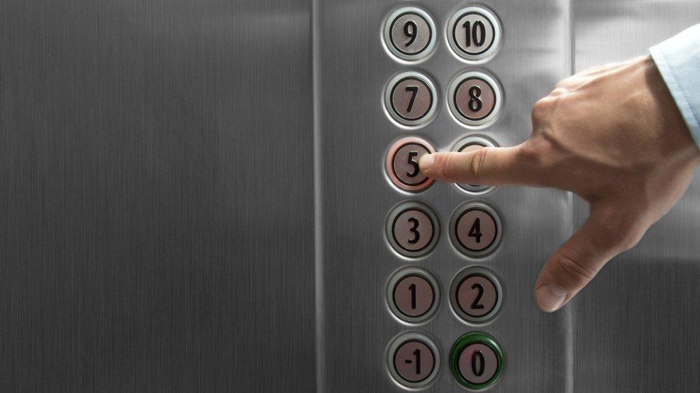 dito di un uomo tocca tastiera di ascensore