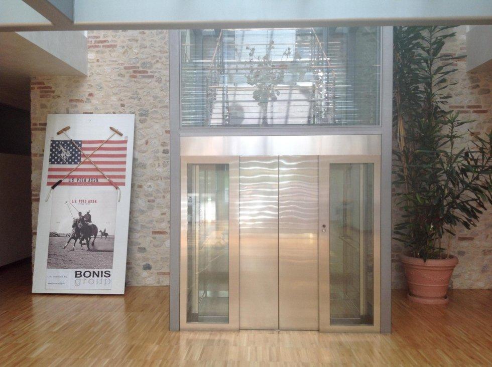 ascensore panoramico all'interno di edificio con pavimento in legno