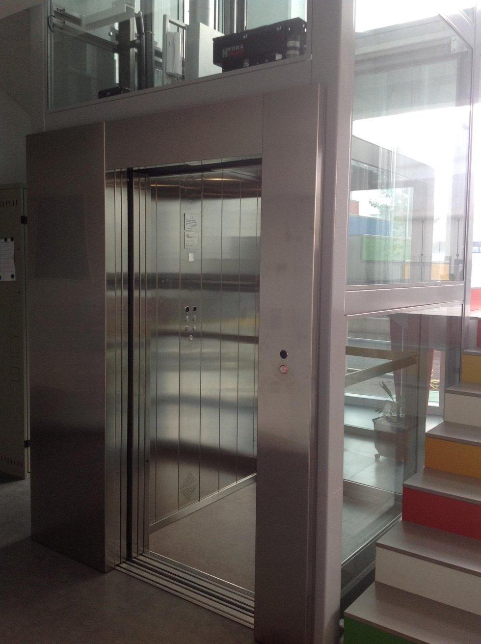 ascensore in vetro e scala con gradini colorati