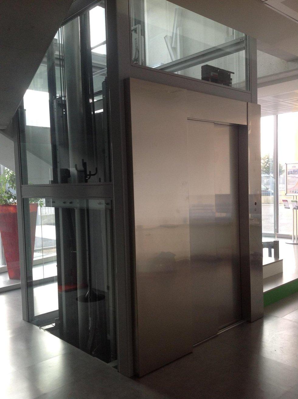 ascensore in vetro con porte chiuse in acciaio inox