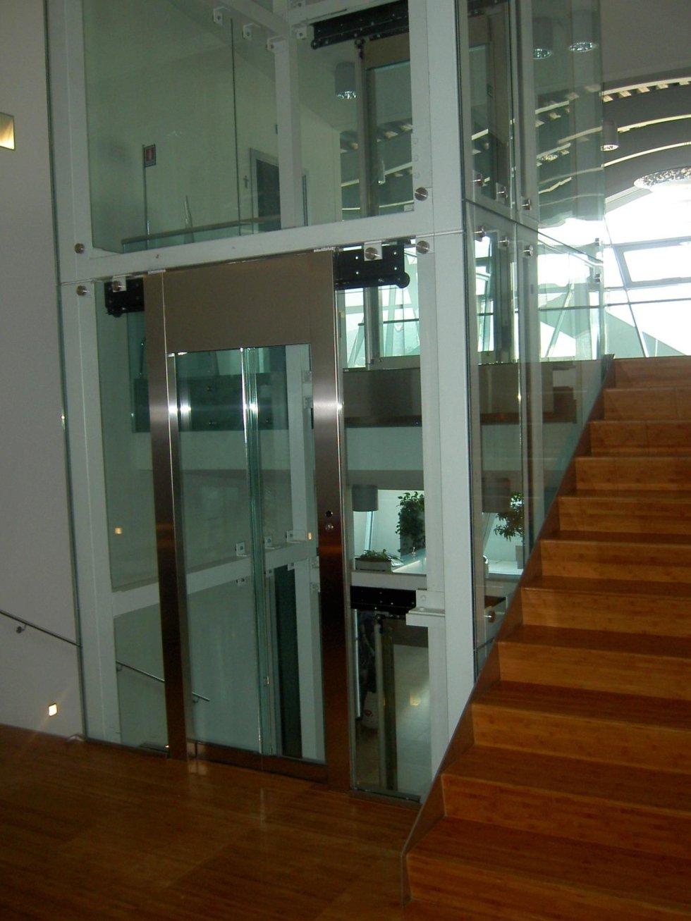 interno di un edificio con scala in legno e ascensore in vetro