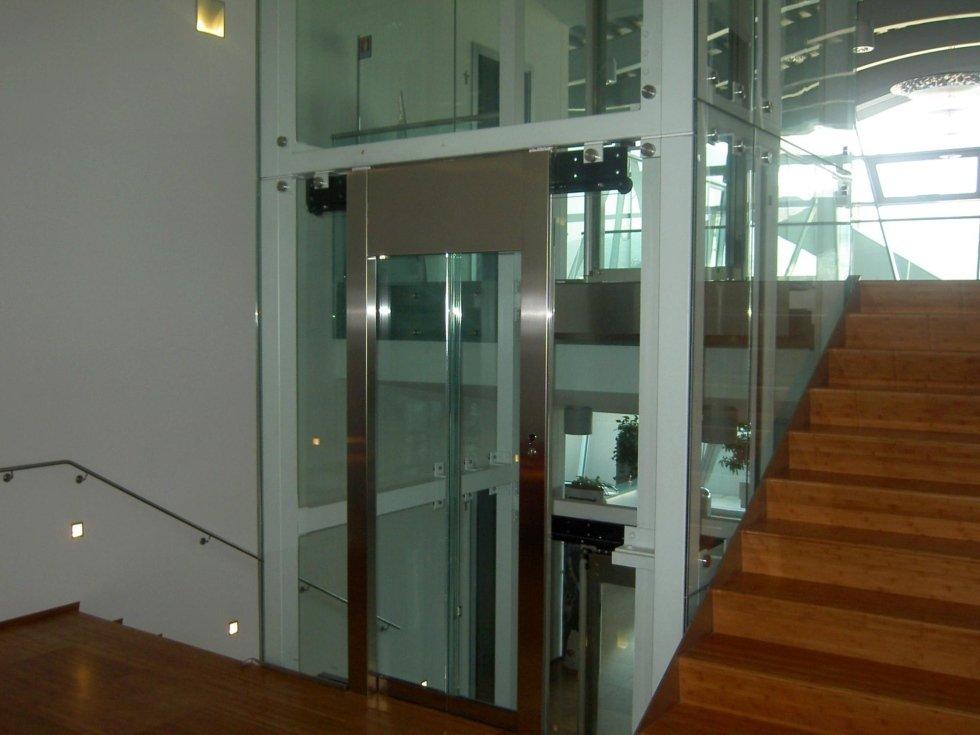 vista interna di un palazzo con scala in legno e ascensore in vetro