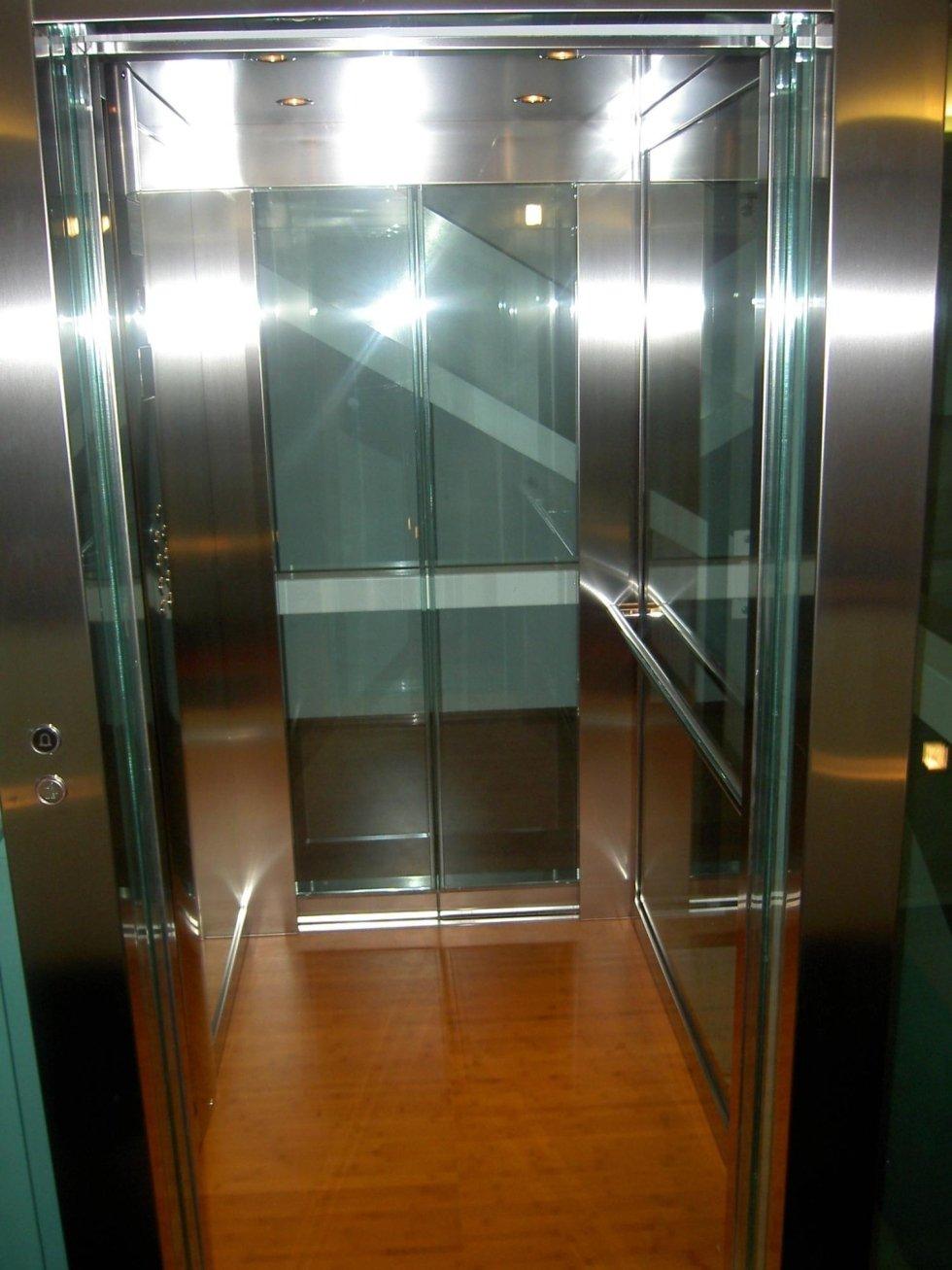 cabina di ascensore in acciaio e vetro, pavimento in legno