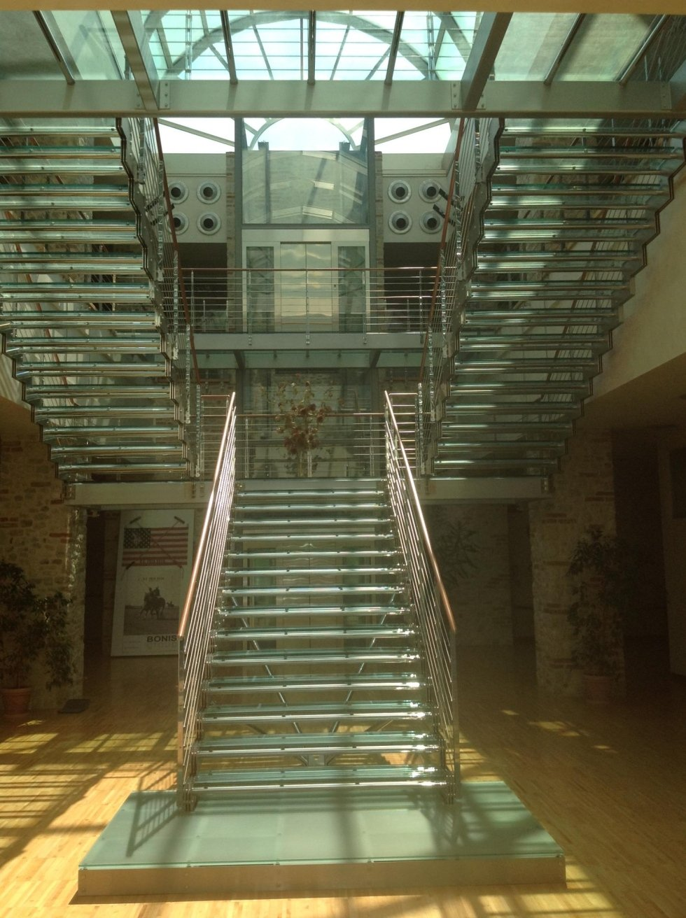 scalinata interna che porta a grande ascensore panoramico in vetro