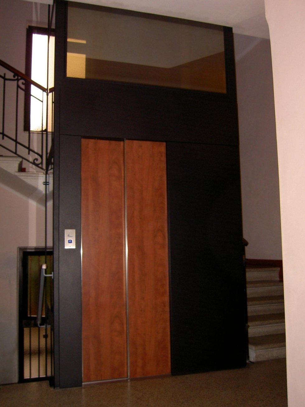 ascensore in legno e scala all'interno di edificio