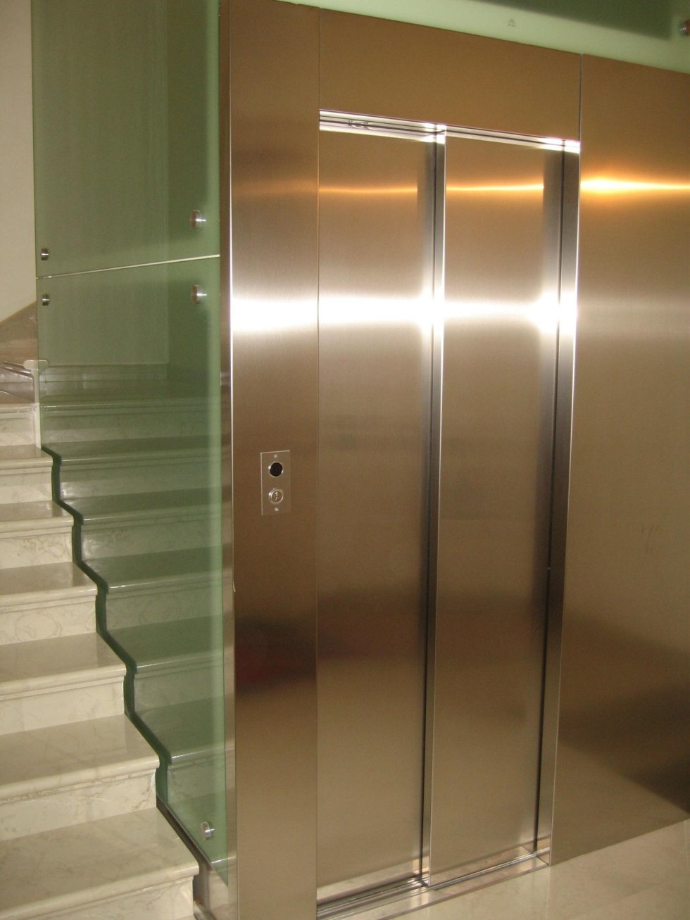 vista interna di palazzo con ascensore in inox e vetro di fianco a scala interna