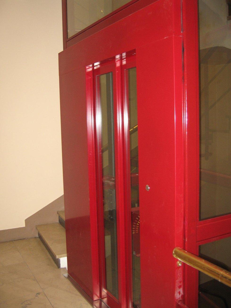 ascensore porte in vetro e profili rossi, vista laterale