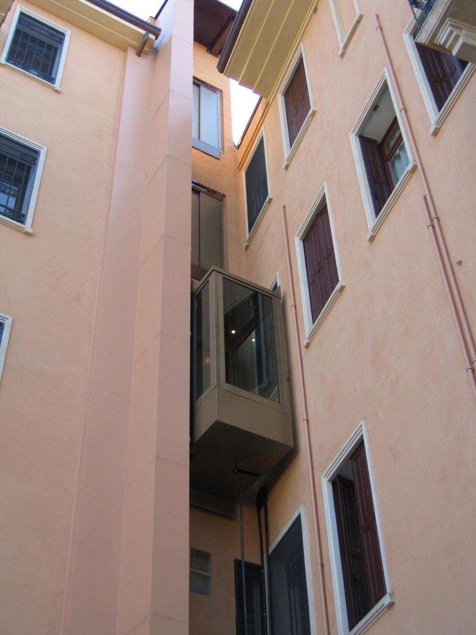 vista dal basso di un edificio rosa con ascensore panoramico