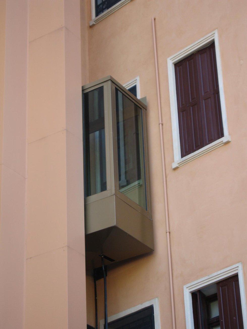 primo piano di un edificio rosa con ascensore panoramico