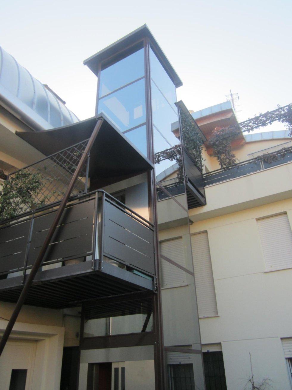 primo piano di ascensore panoramico esterno in palazzina beige