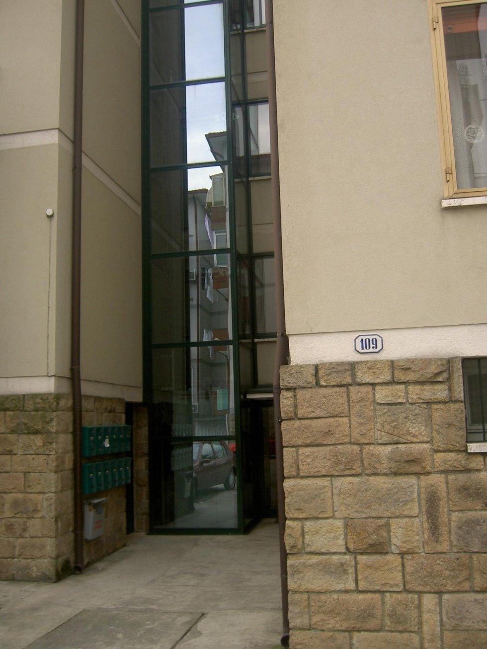 ascensore esterno per condominio con parete in pietra