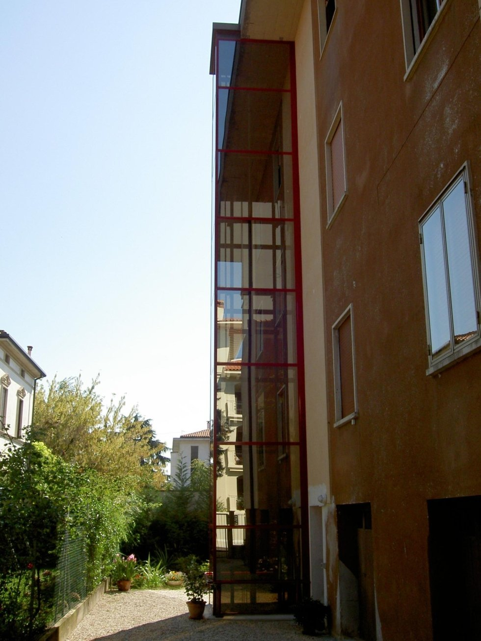 vista laterale di un edificio con ascensore  panoramico in vetro e profili rossi