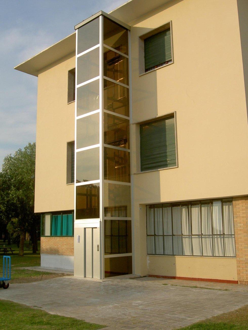 vista angolare di un edificio giallo con ascensore in vetro, persiane e giardino