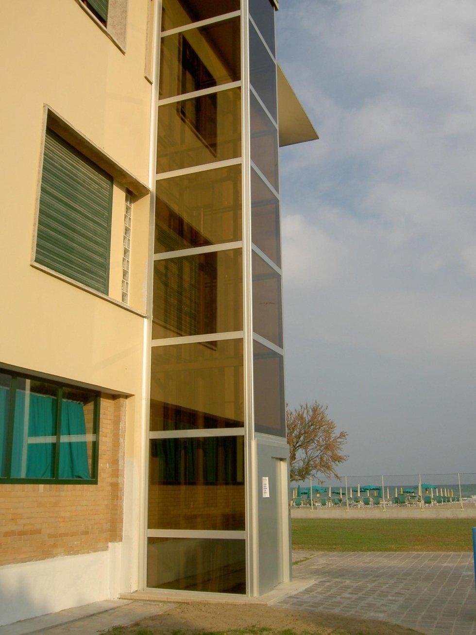 vista laterale di un edificio giallo con ascensore in vetro