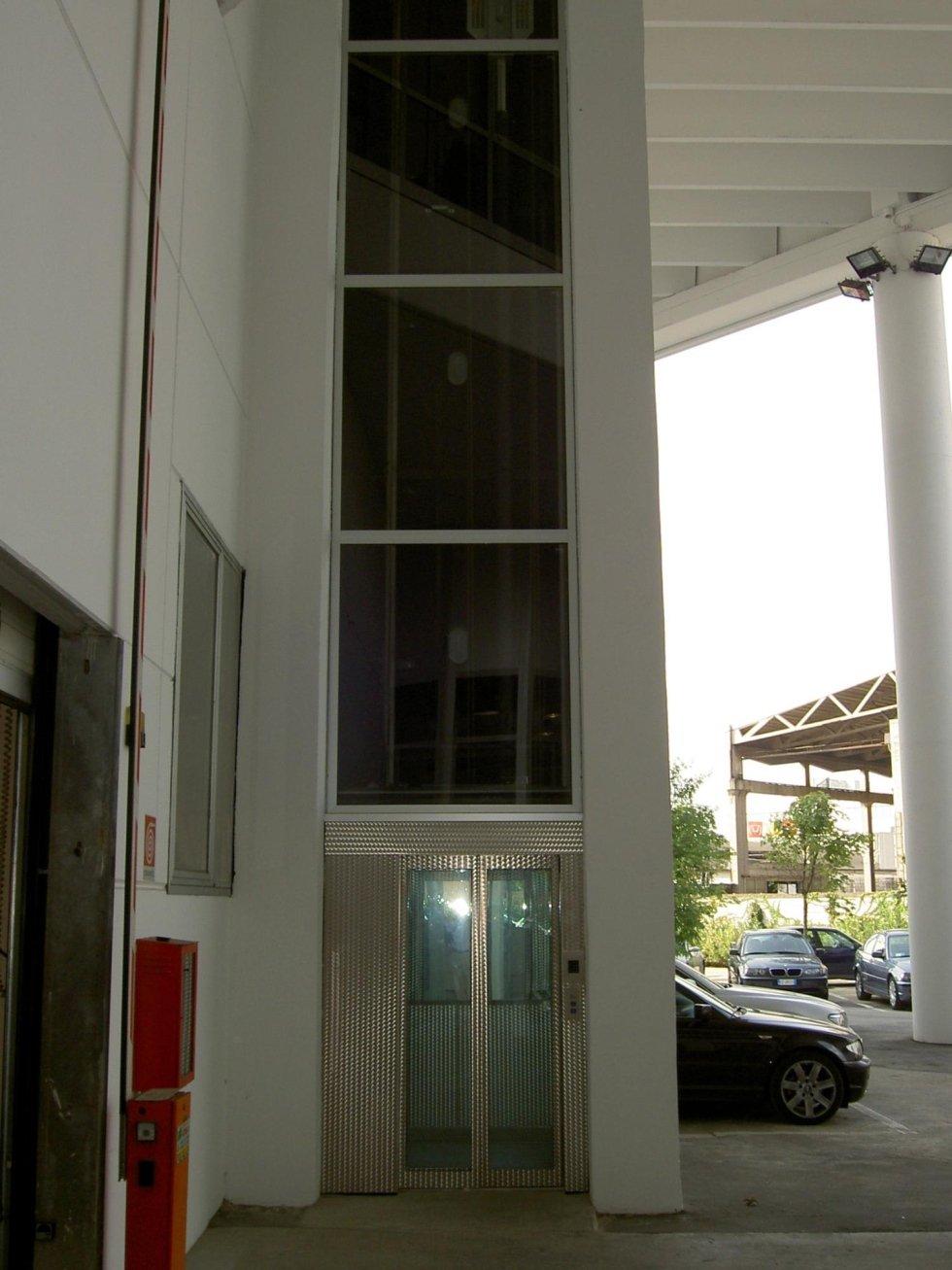 vista laterale di un edificio con ascensore e macchine parcheggiate