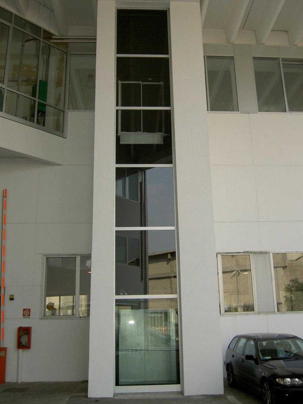 vista esterna di un edificio con ascensore in vetro e finestre in vetro e una macchina parcheggiata