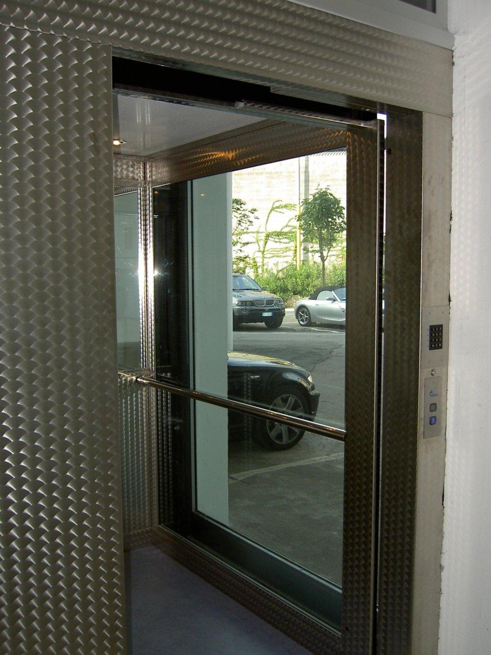 ascensore panoramico in vetro esterno e macchine parcheggiate