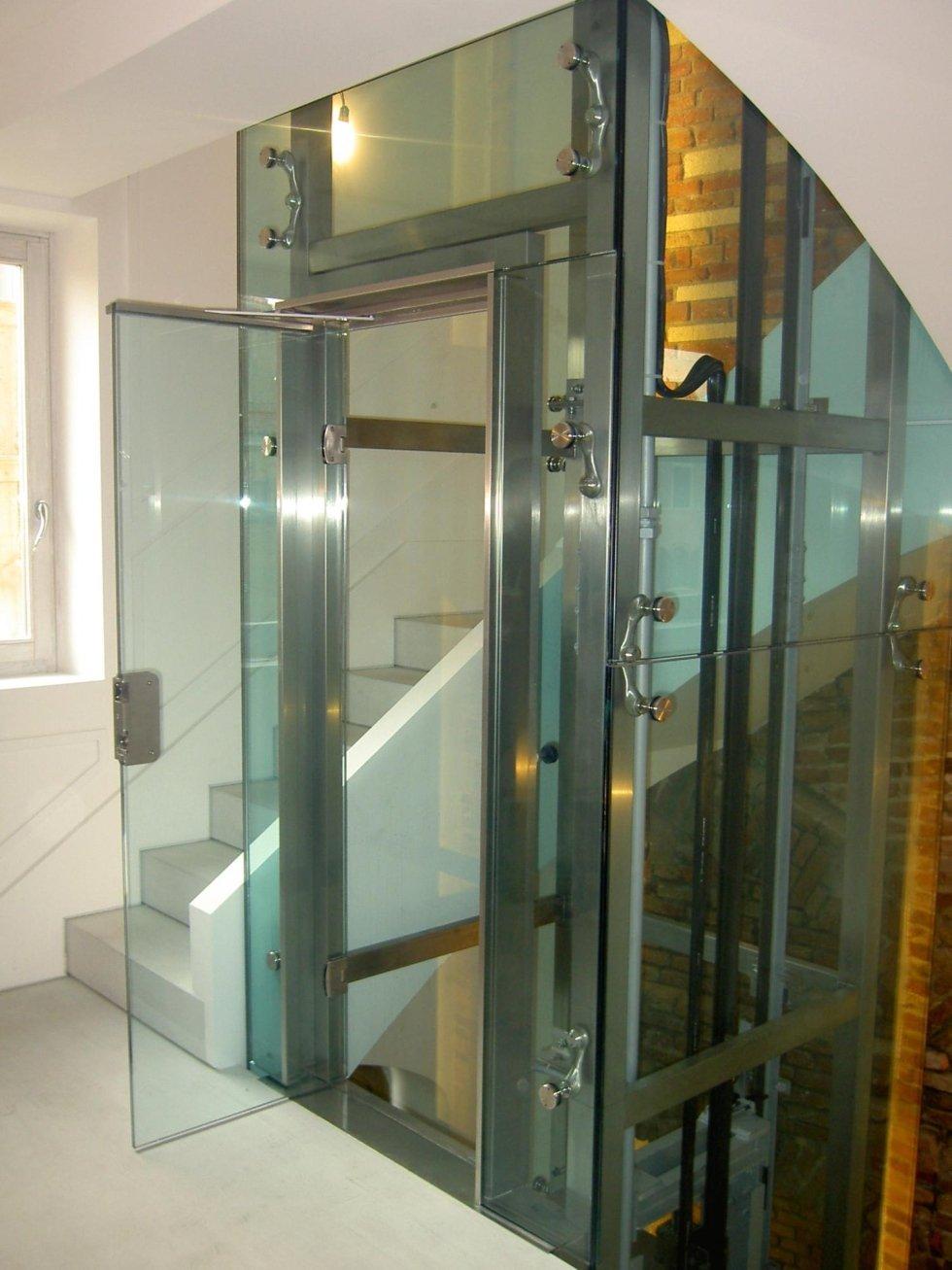 Piattaforme elevatrici per una casa in vetro con una porta aperta