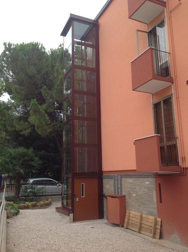 vista laterale di una casa con piattaforma elevatrice per esterno e alberi