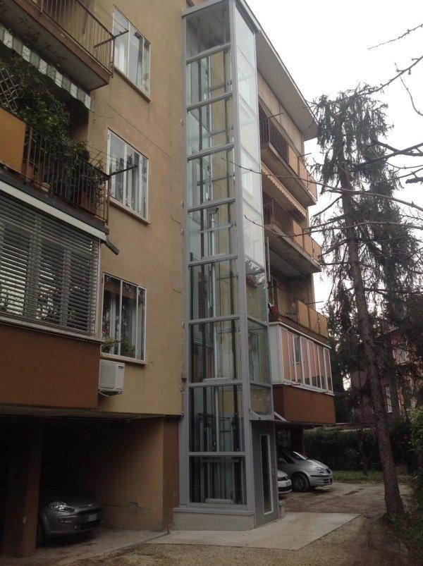 piattaforma elevatrice panoramica in una casa con macchine parcheggiate giù-vista laterale