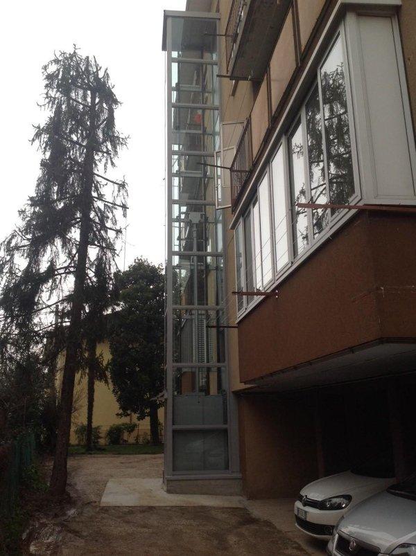 piattaforma elevatrice panoramica in una casa con macchine parcheggiate giù