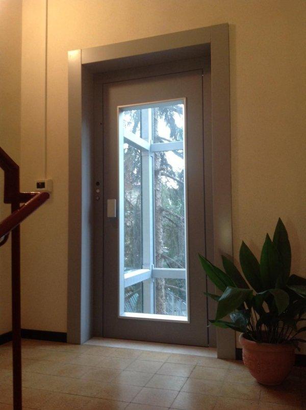 piattaforma elevatrice per esterno con porta di piano in vetro e parete gialla