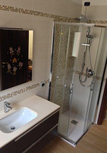 un bagno con un box doccia e pavimento in legno