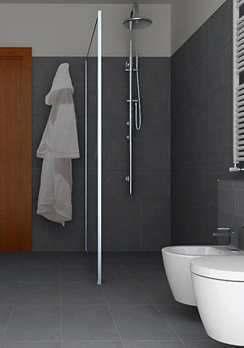 una doccia con divisorio, un bidet e un wc