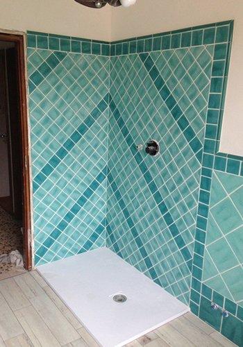 un angolo con piastrelle azzurre ai muri con piatto doccia sotto