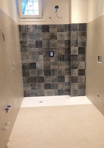 delle piastrelle beige,nere,grigie e marroni in una doccia