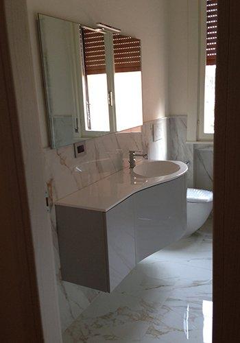un lavabo con sotto un mobiletto e sopra una specchiera