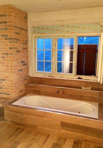 un bagno  con il parquet e vista di una vasca