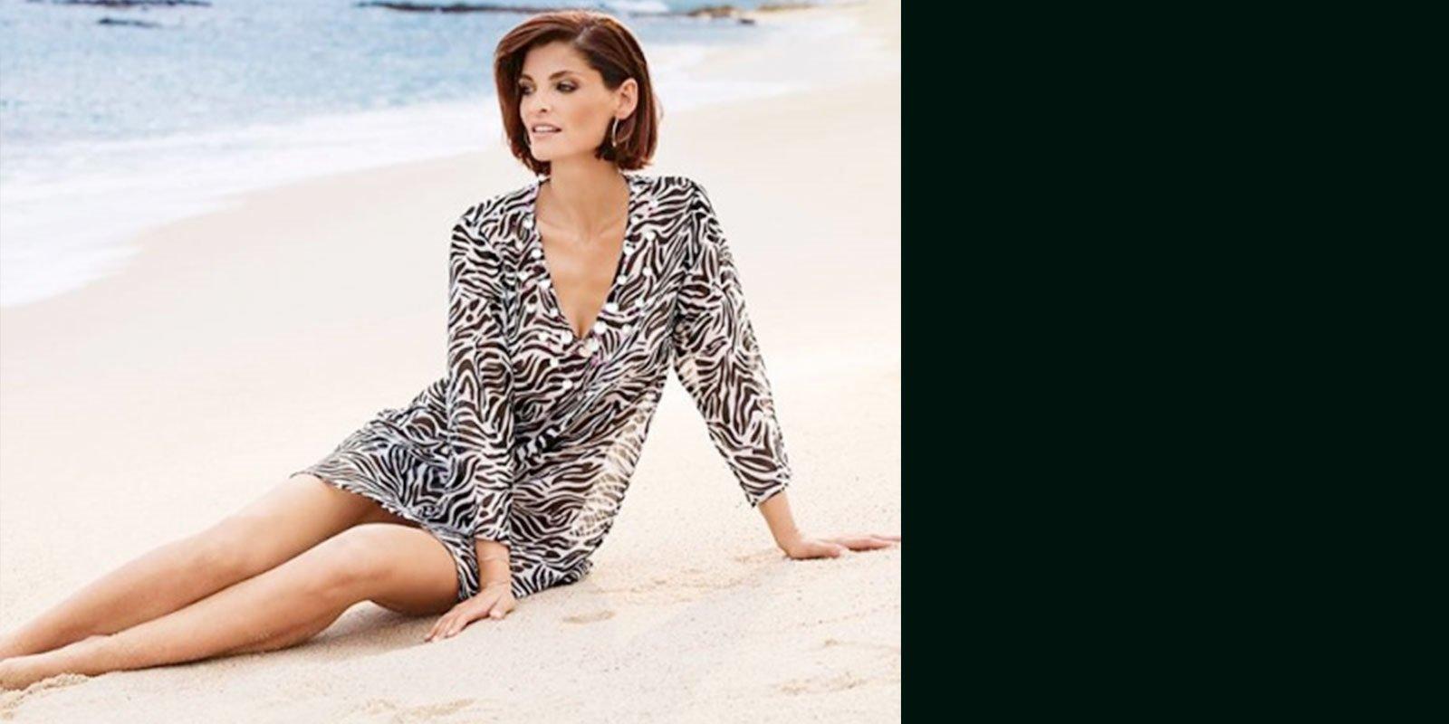 una donna seduta su una spiaggia con una camicia con  disegni tigrati