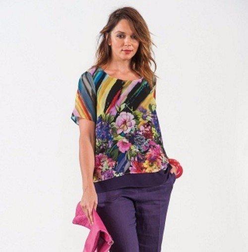 una donna con dei pantaloni di color viola e una camicia con disegni a fiori