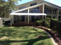 shades of blue shade sails house with beautiful garden