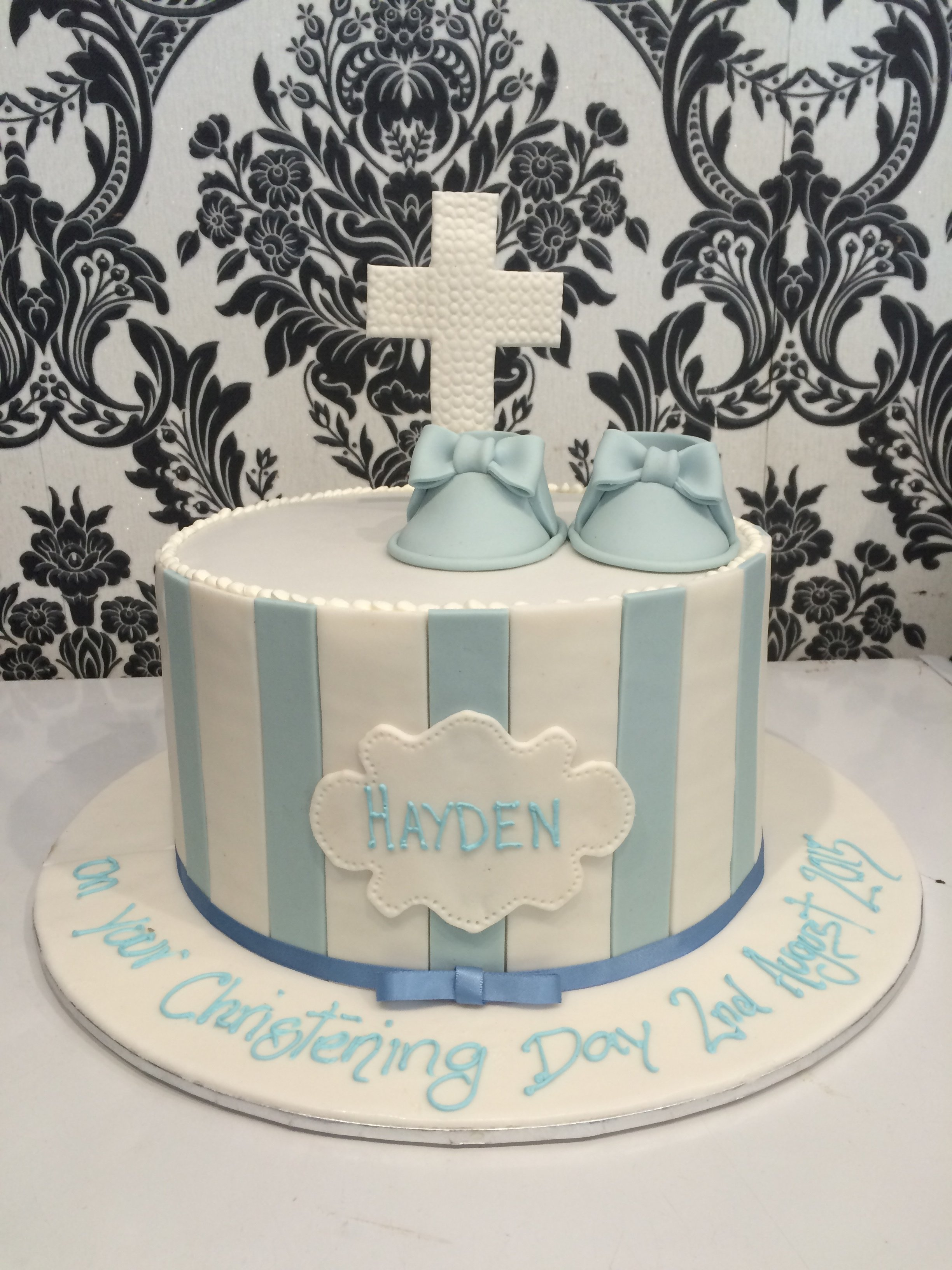 white christening cake with white cross on top and blue panels