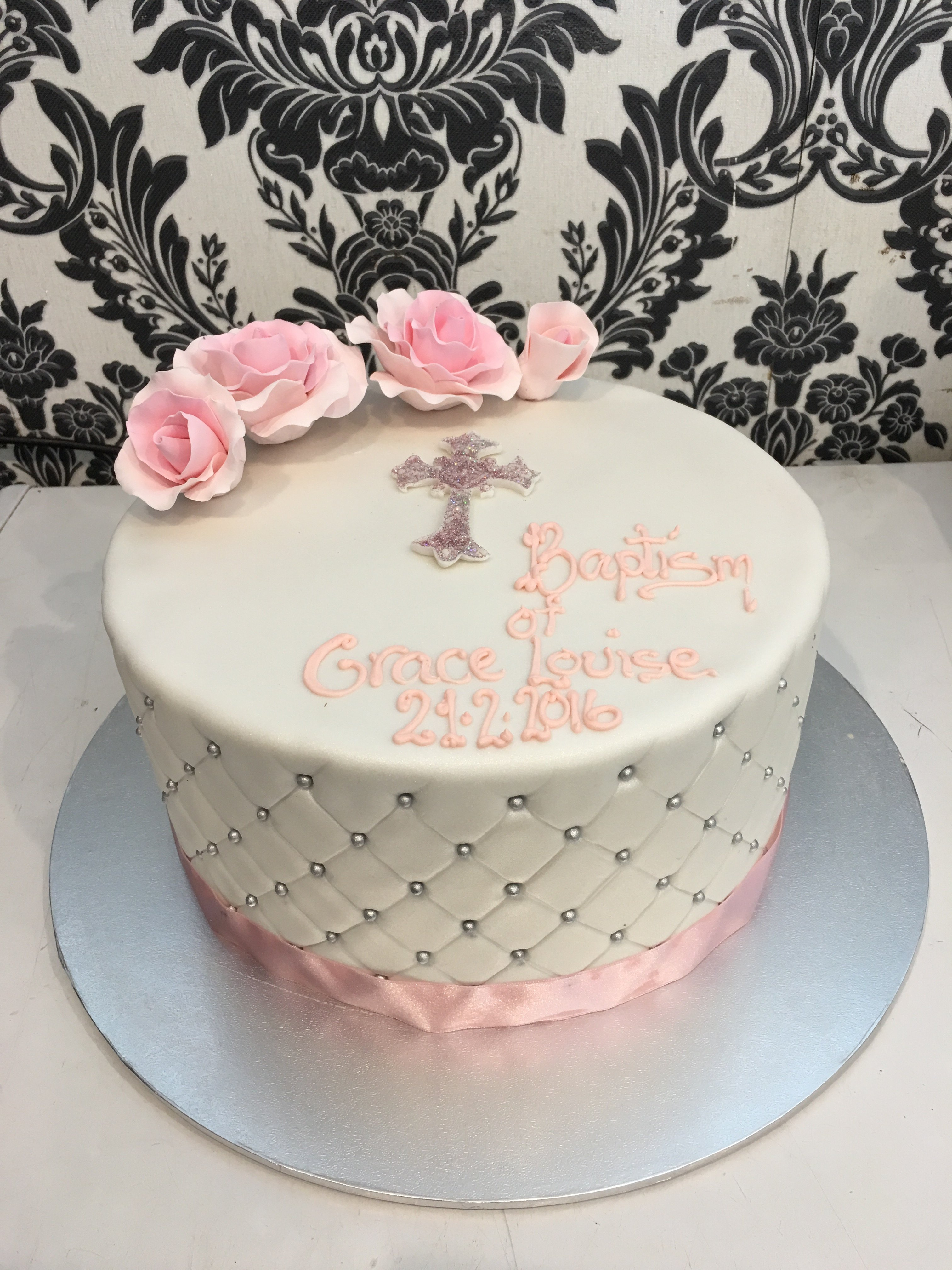custom white double layer christening cake with pink bow and ribbon