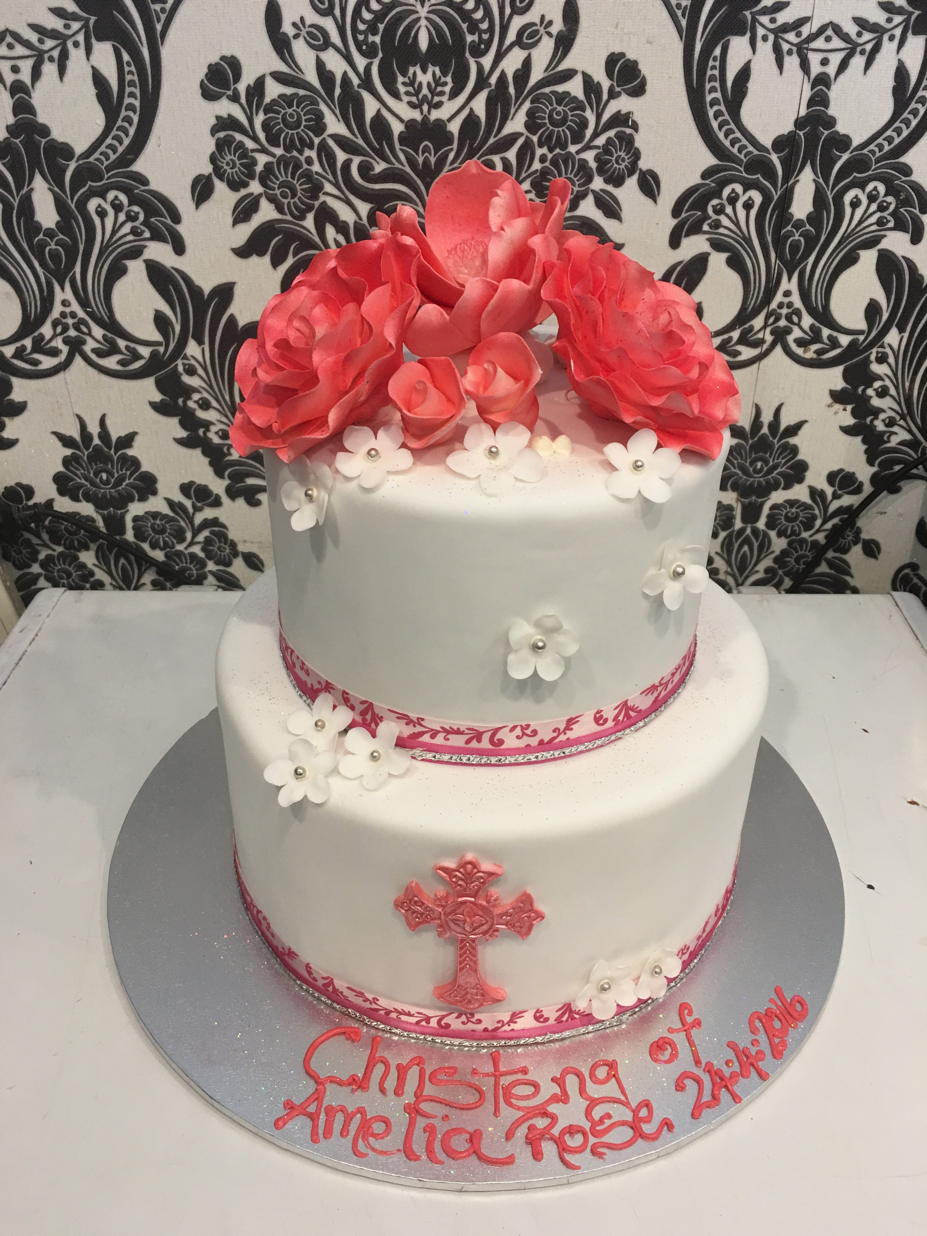 white double layer christening cake with red cross and flowers