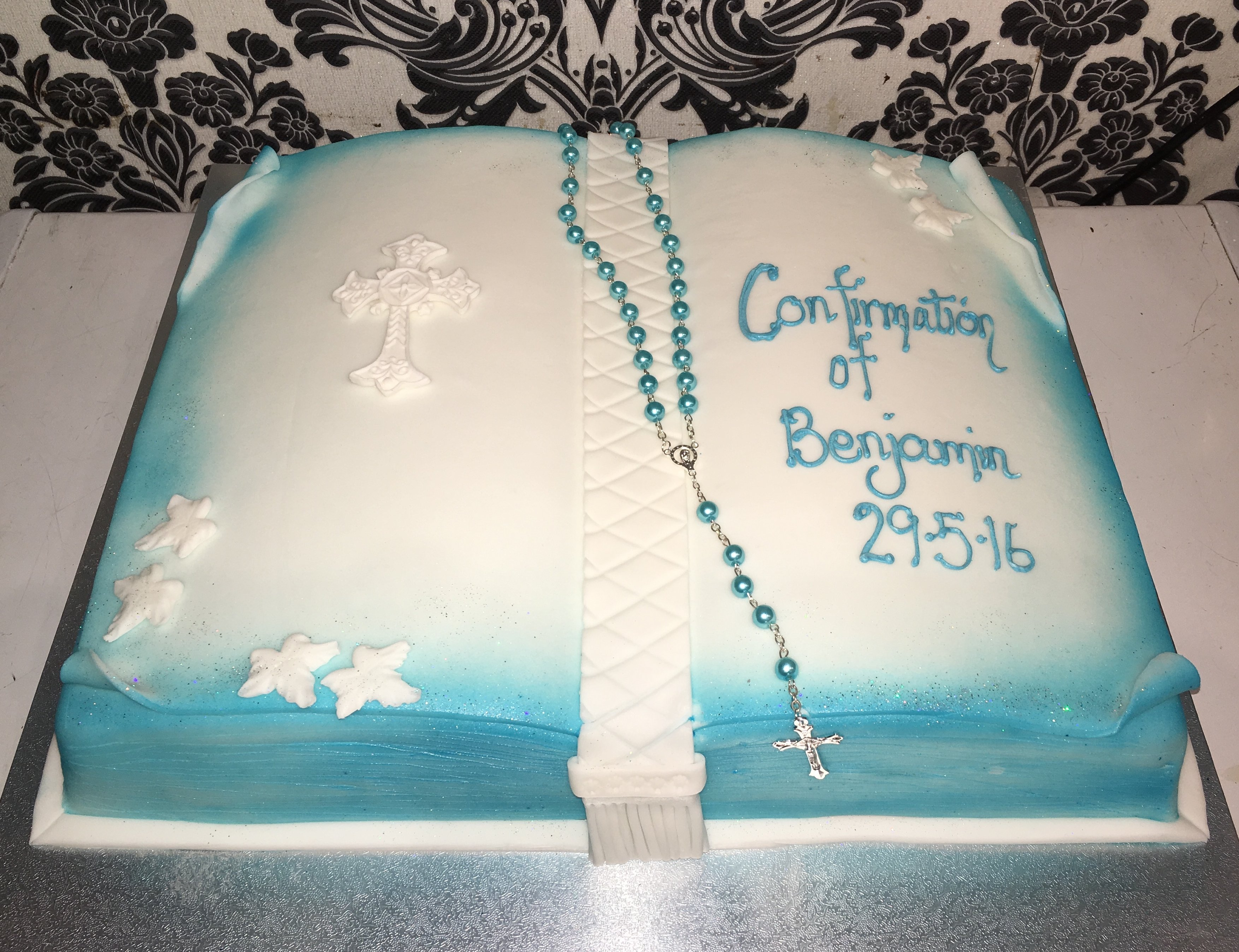 white confirmation book cake with blue edges and white stars