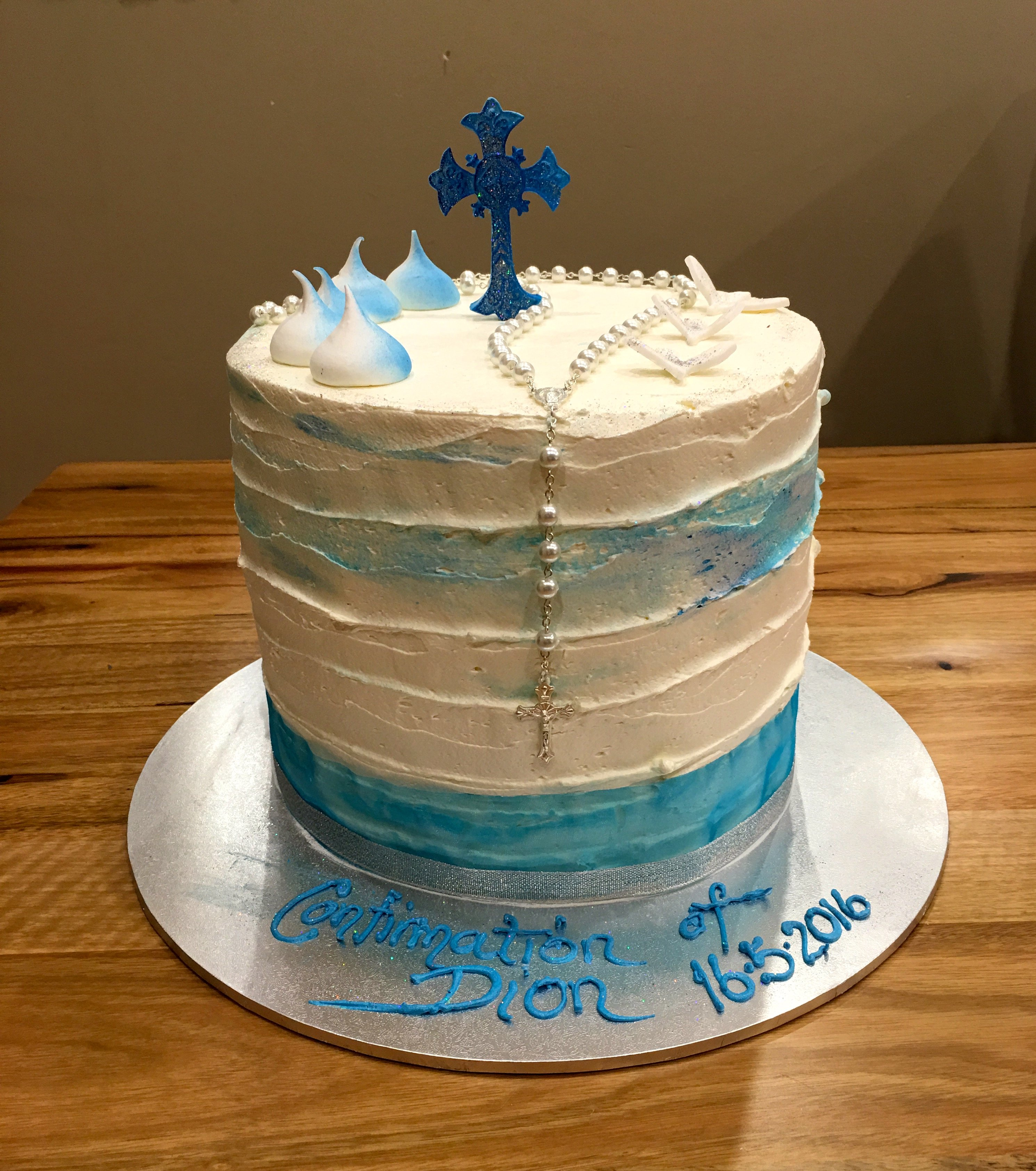 white and blue stacked cake with blue details and cross